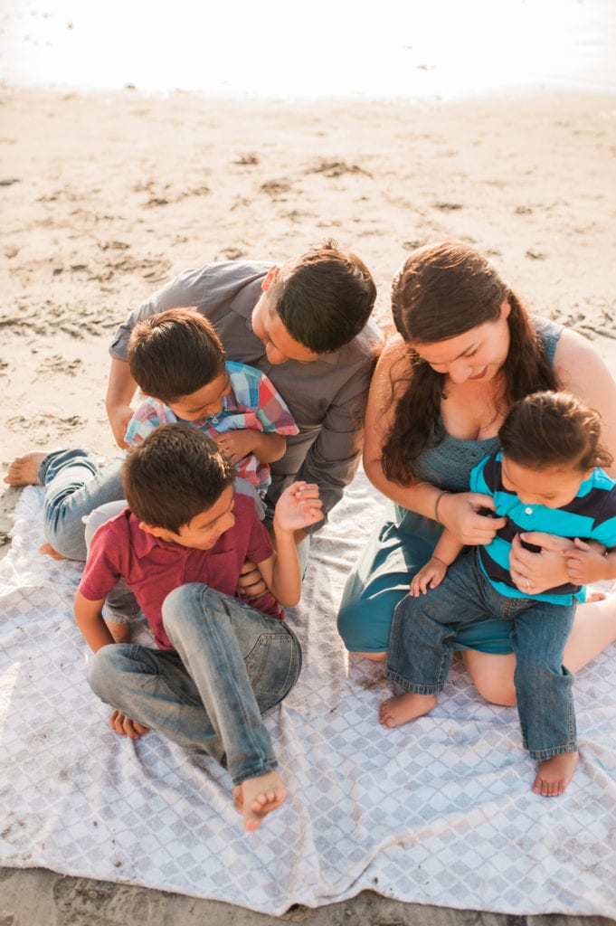 family sitting on the beach together laughing